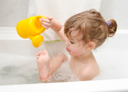 Little Girl is taking a bath, playing with a toy watering-can.